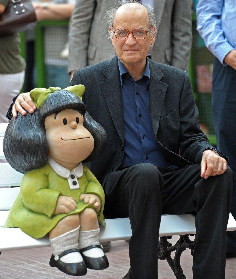 Quino sentado junto a la estatua de Mafalda en el Paseo de la Historieta, en el barrio de Monserrat<br>