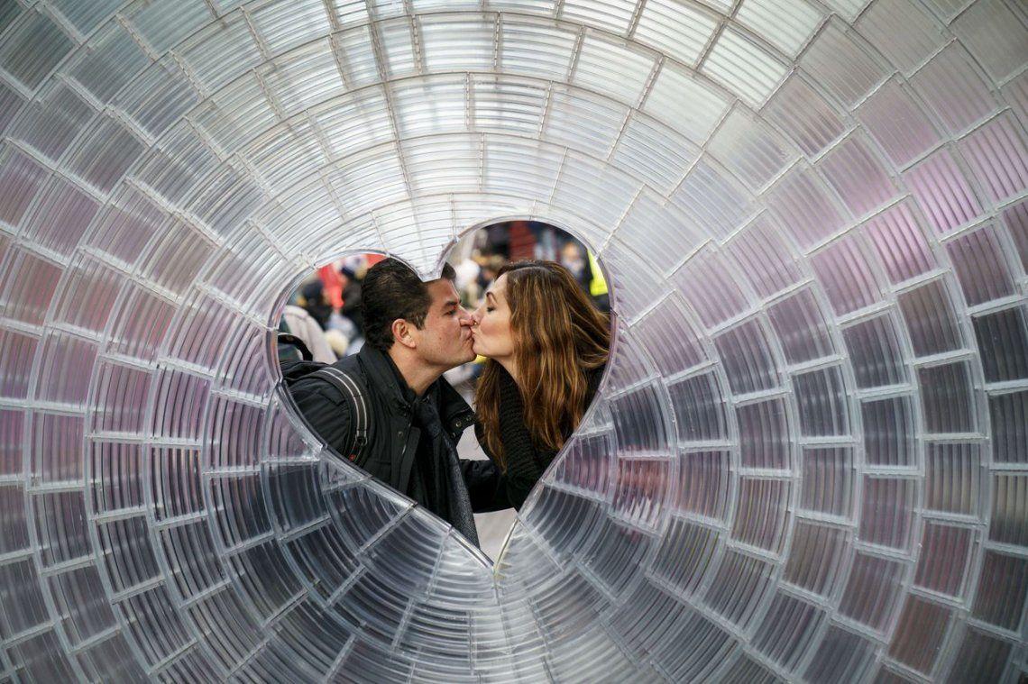 Una pareja se besa frente a la instalación Window To The Heart