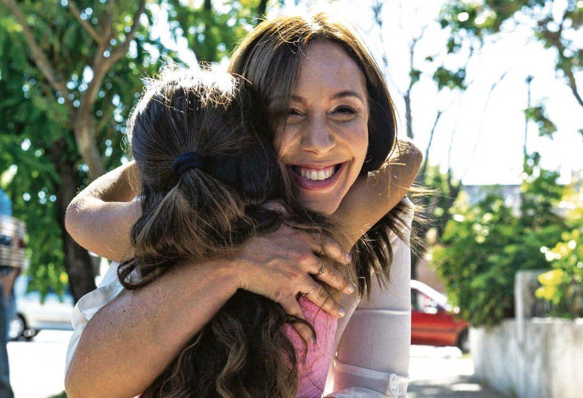 dLa gobernadora Vidal recibe el afecto de una niña durante su recorrida por un barrio de José León Suárez.