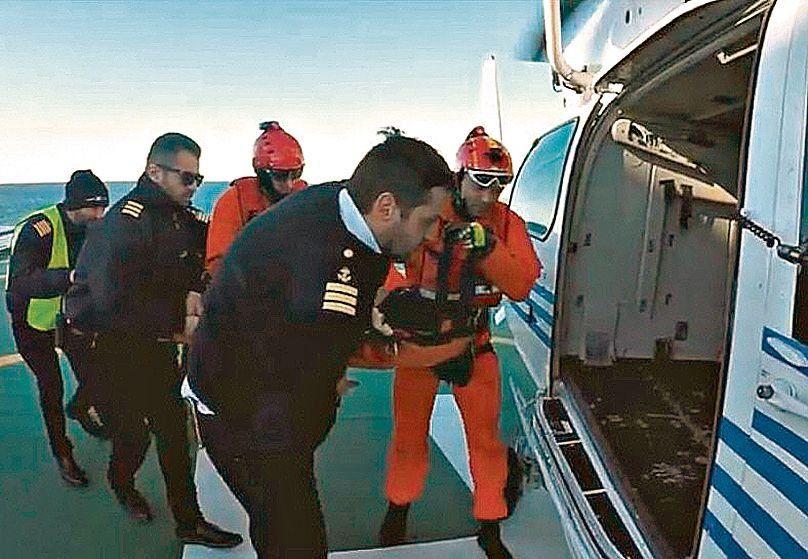 dPrefectos ingresan al tripulante infartado al helicóptero.