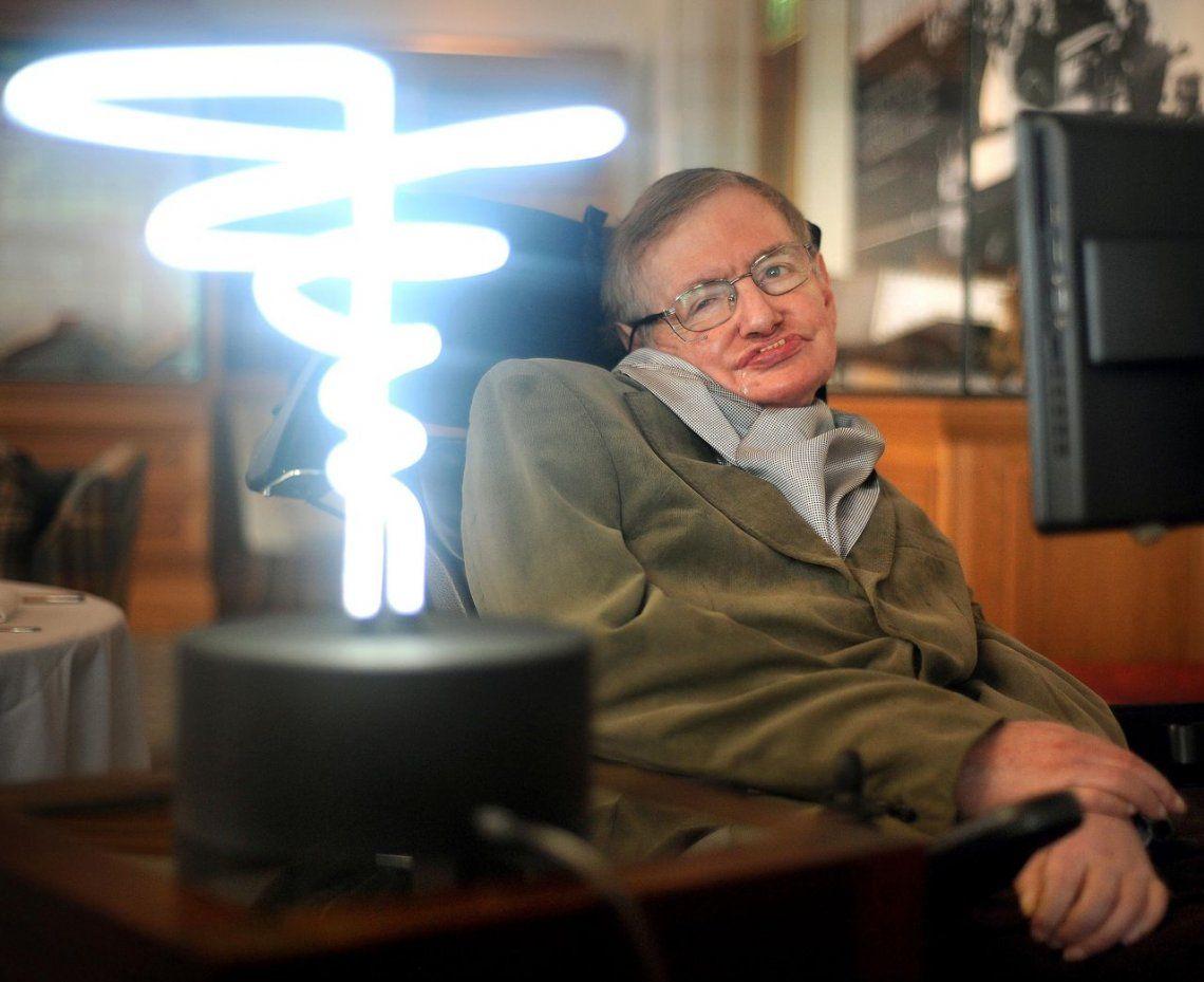 Stephen Hawking posa junto a una lámpara titulada luz de agujero negro del inventor Mark Champkins