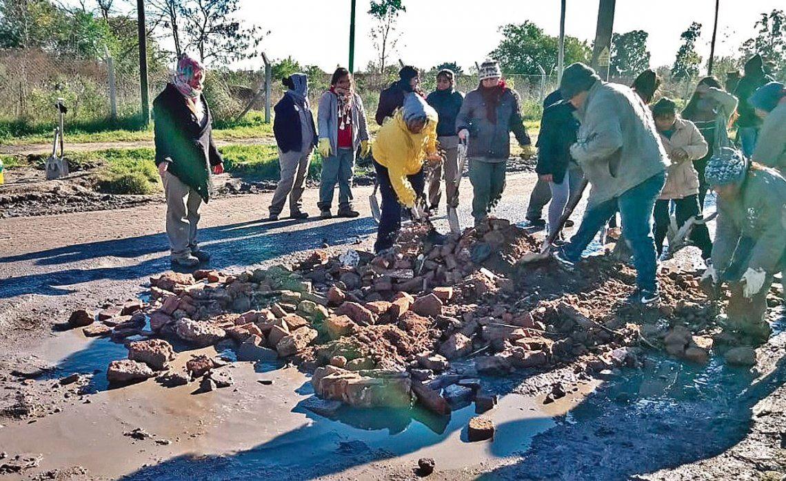 dLa imagen es más que elocuente: los vecinos unidos para trabajar cubriendo los baches de las calles.