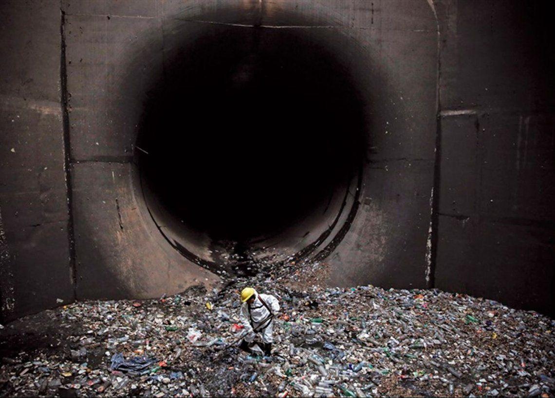 Un operario retira basura del canal aliviador del arroyo Maldonado.