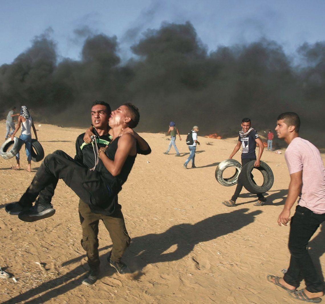 dUn manifestante evacua a un joven herido durante los enfrentamientos.