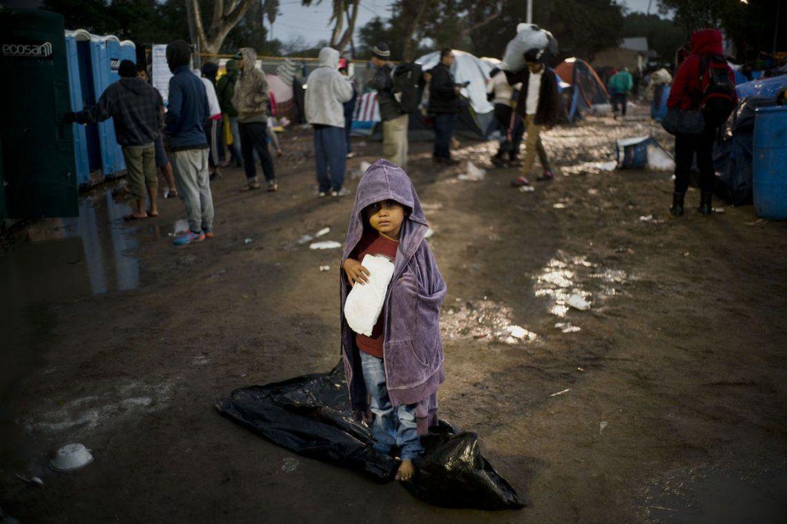 Un niño migrante camina bajo la lluvia