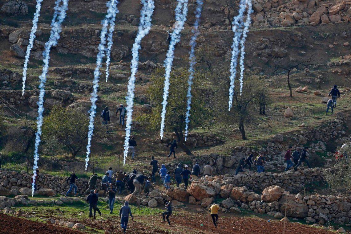 Palestinos se protegen del humo de gas lacrimógeno disparado por las fuerzas israelíes
