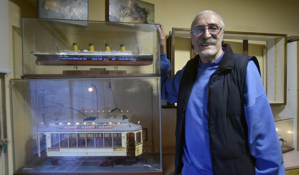 Soldano posa junto a dos de sus maravillosas réplicas: el Titanic y el vagón de subte.
