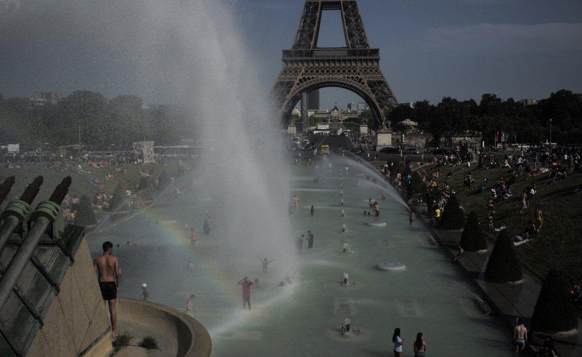 La gente busca un alivio en las fuentes de los jardines frente a la Torre Eiffel