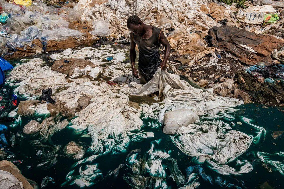 Un hombre enjuaga bolsas de plástico en un vertedero de basura en un pantano