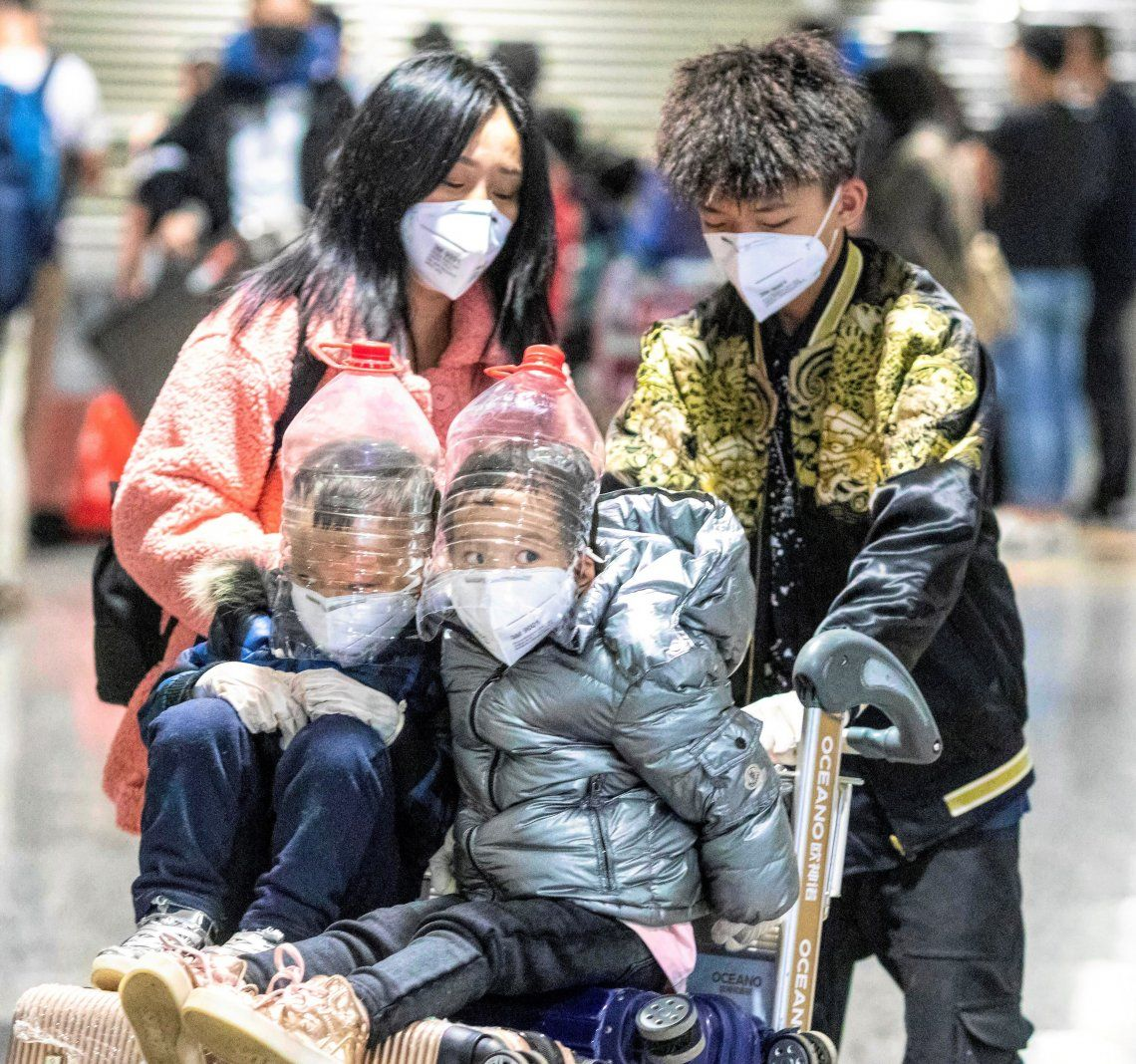 Dos niños con protecciones improvisadas en el aeropuerto de Cantón