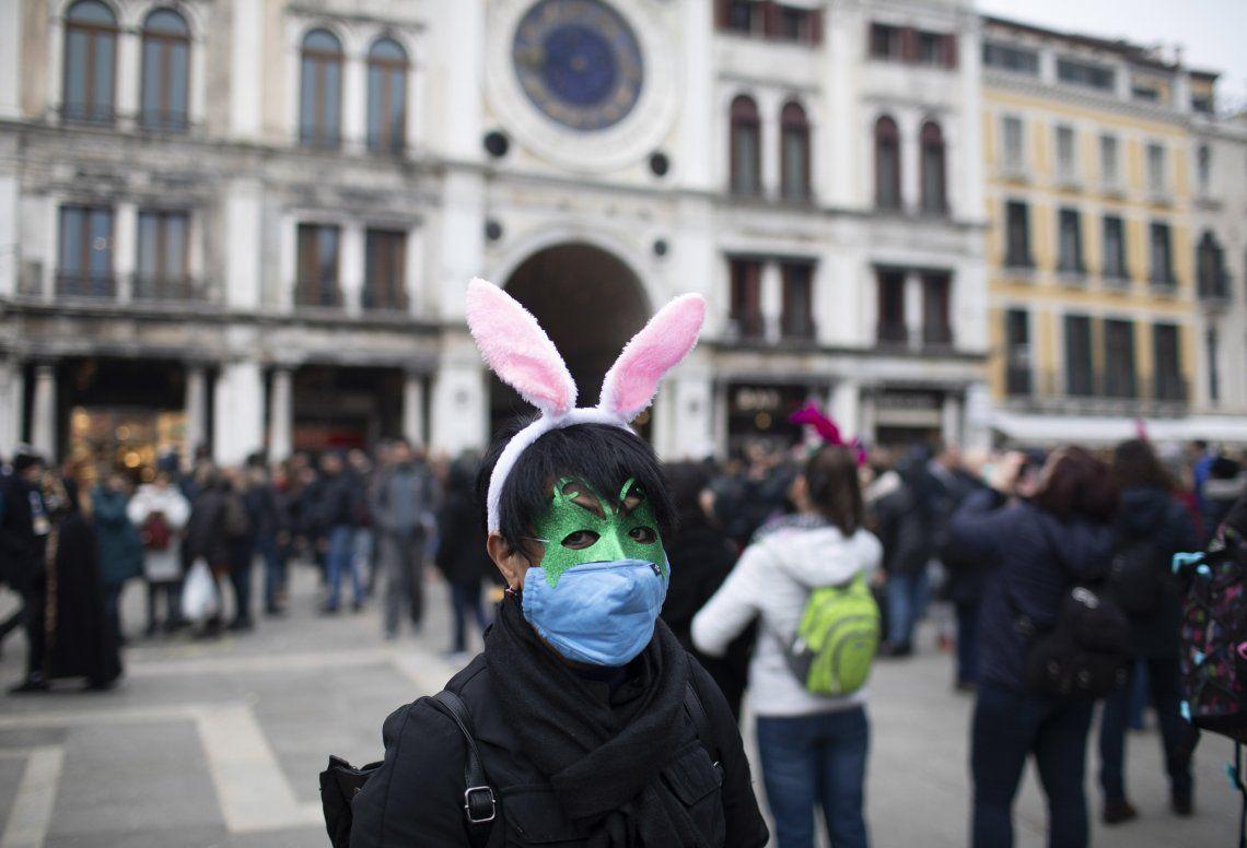 Una ciudadana asiática vestida para el Carnaval de Venecia pero protegida con un barbijo.