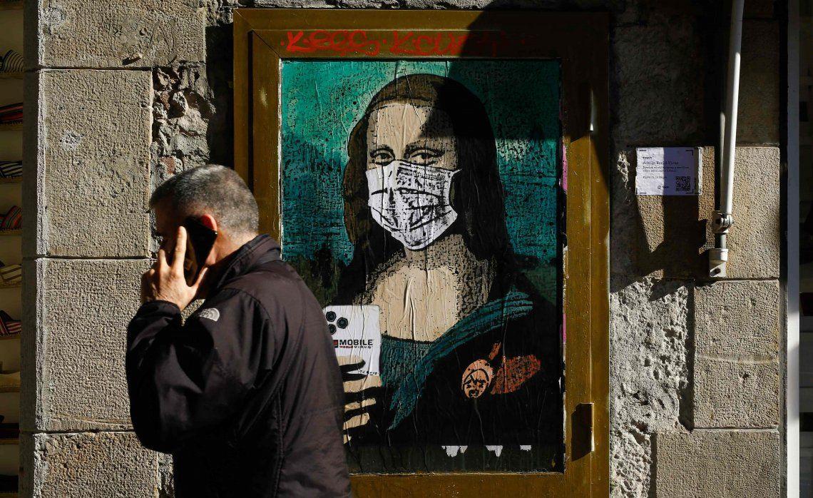 Un ciudadano español pasa delante de un cuadro con una Gioconda protegida con un barbijo.