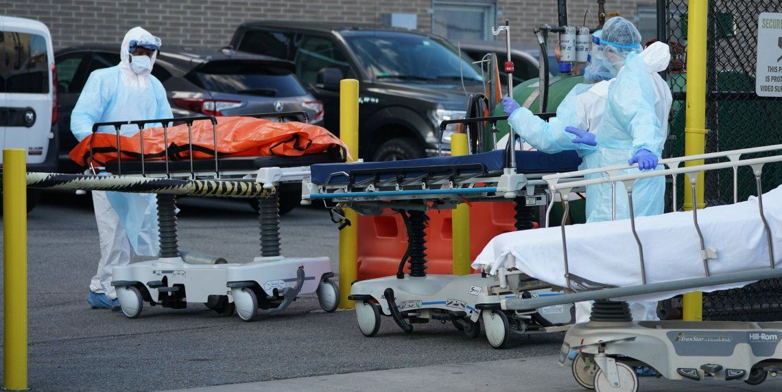 Personal sanitario traslada a una de las víctimas hasta los camiones refrigerados que operan como morgues.