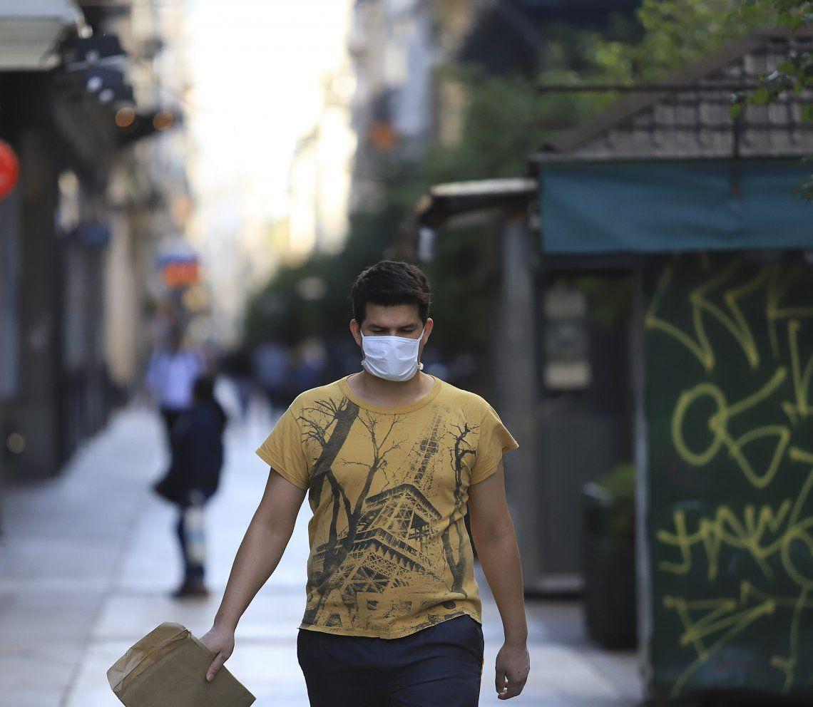 Un joven camina con barbijo por la city porteña.