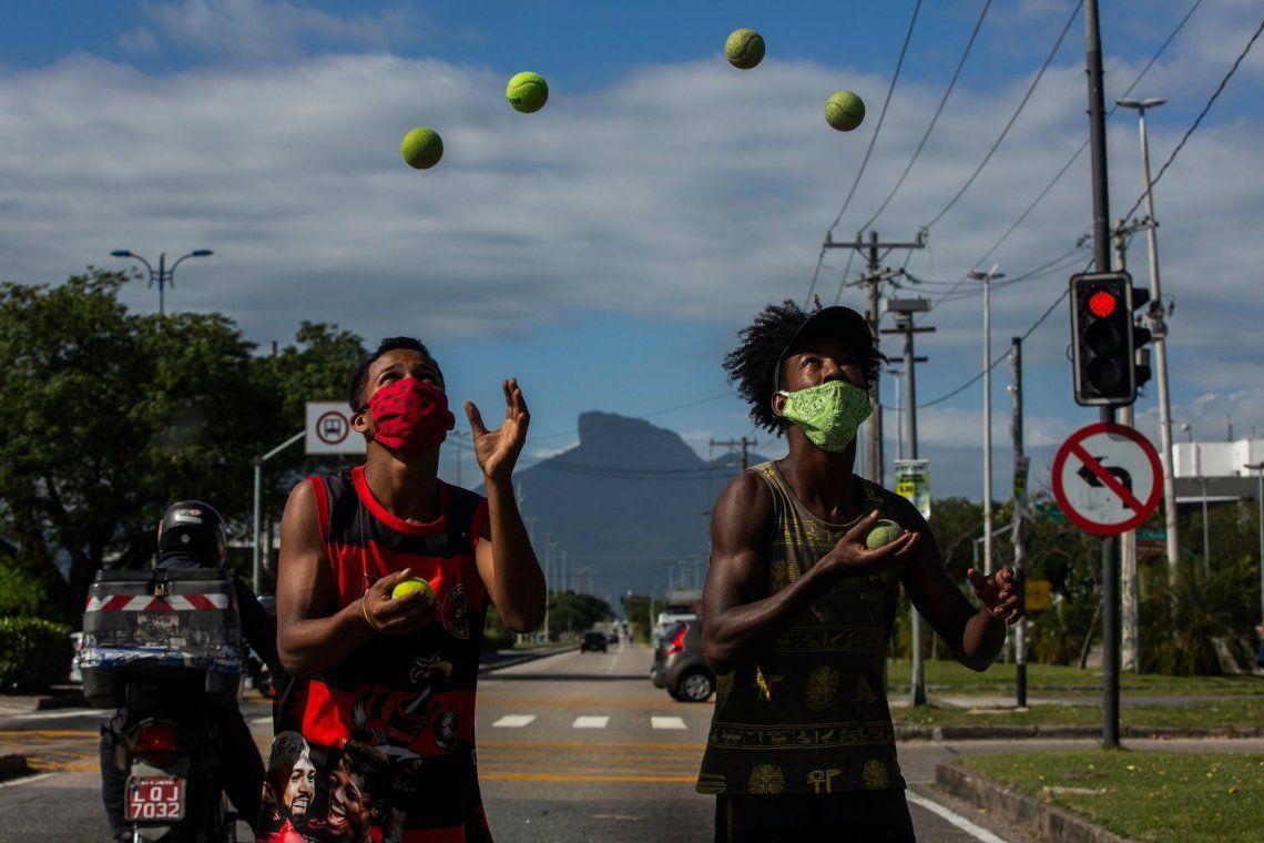 Niños con tapa boca hacen malabares con pelotas de tenis en el semáforo en Barra da Tijuca