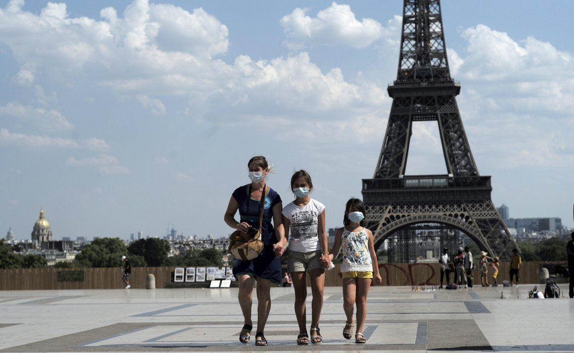 Una madre camina junto a sus dos hijas tras haber visitado la Torre Eiffel. Las tres llevan puesto barbijo.