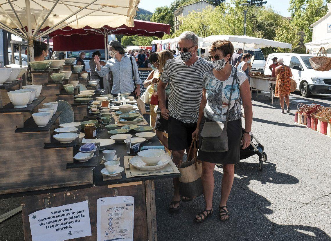 Una pareja observa productos en un mercado francés de Malaucene.