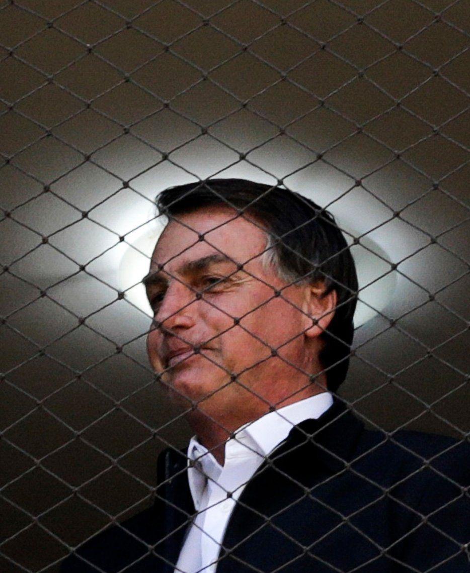 Bolsonaro observa a sus seguidores desde una ventana.
