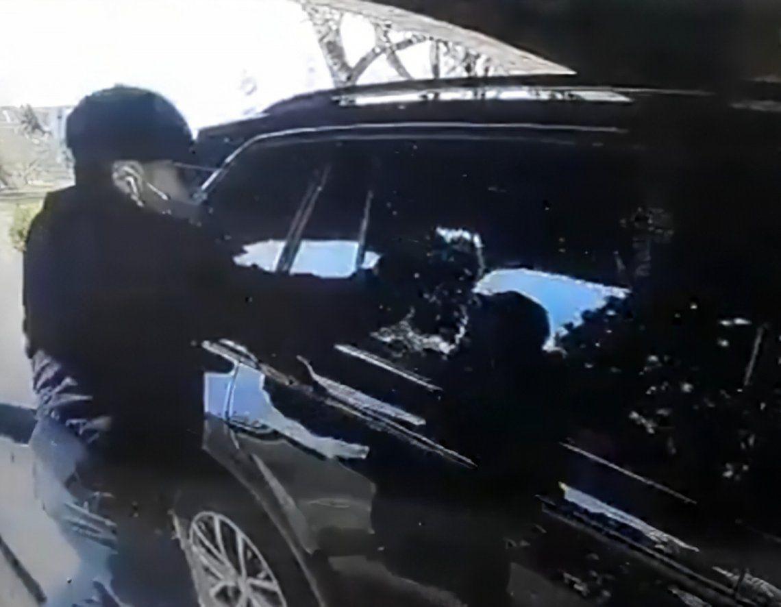 La imagen capta el momento justo en que el motochorro rompe el vidrio del auto en el ingreso del country.