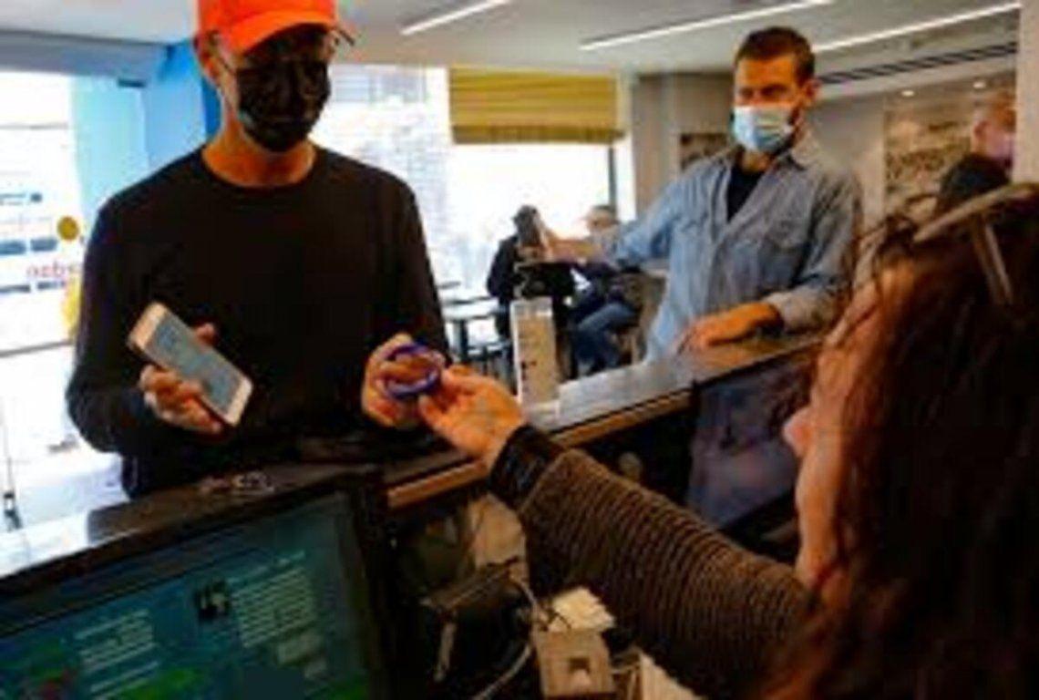 Un hombre muestra el código del pase verde que indica que recibió las dos dosis de la vacuna para entrar en un gimnasio.
