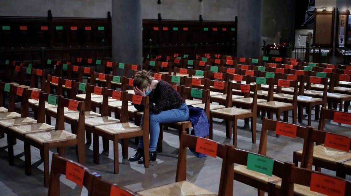 Un devoto reza mientras se colocan calcomanías para respetar el distanciamiento social en los asientos después de un servicio del Jueves Santo de Pascua en la iglesia de Saint Pierre de Montrouge
