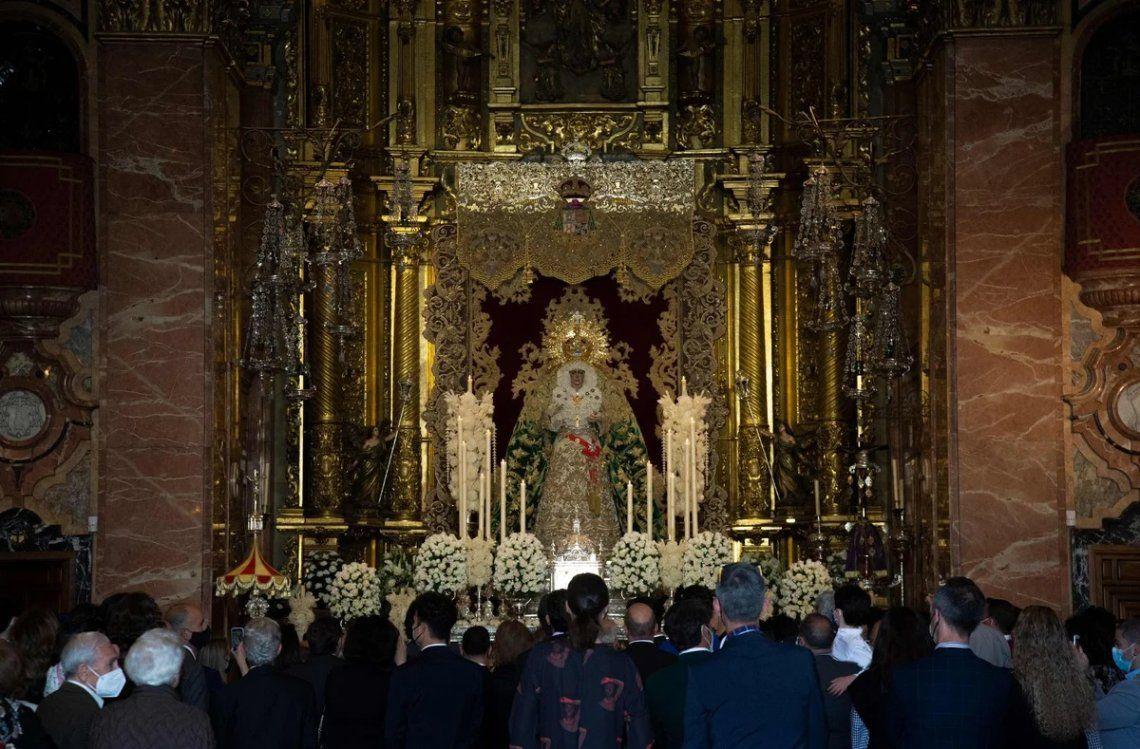 Visitantes observan la figura de la Virgen Macarena en la basílica de la Macarena