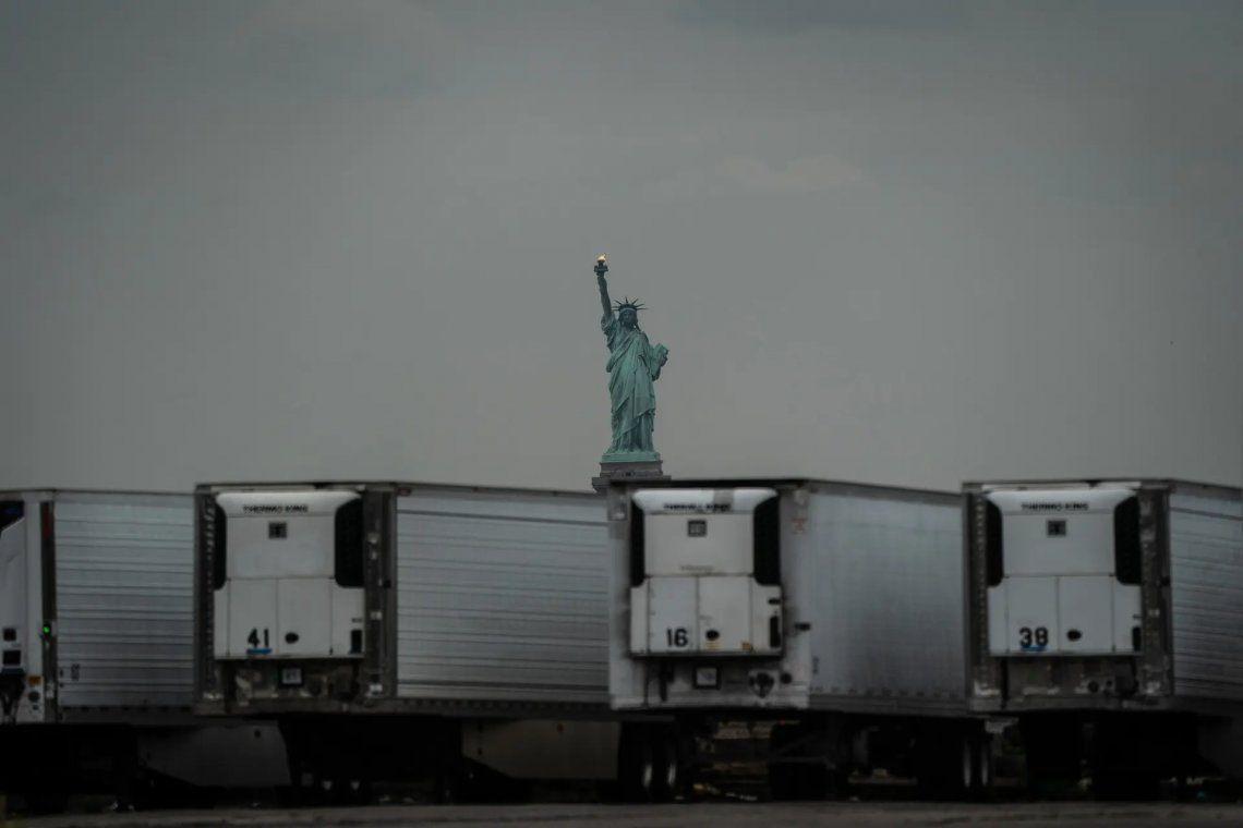 Estatua de la Libertad detrás de los remolques refrigerados temporales de la morgue del coronavirus. Fotografía: Adam Gray / SWNS