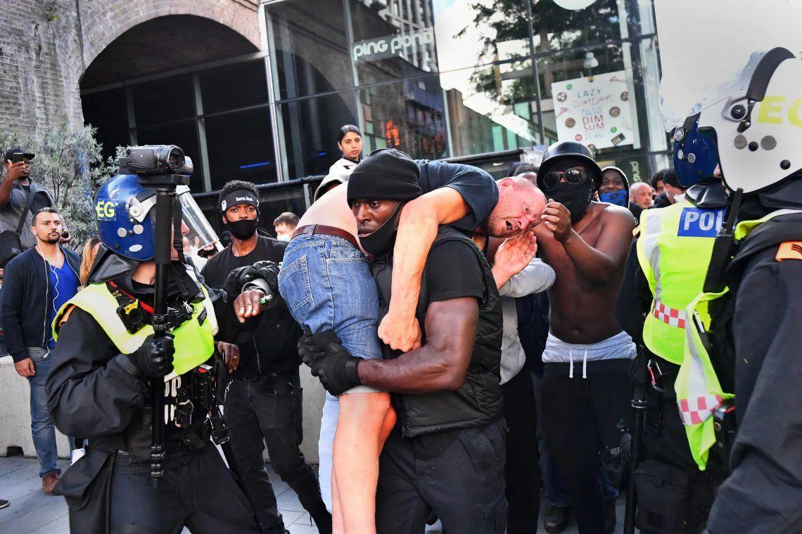 Ganador del fotógrafo de noticias del año. Un manifestante lleva a un contramanifestante herido a un lugar seguro cerca de la estación de Waterloo de Londres durante una protesta de Black Lives Matter en junio de 2020. Fotografía: Dylan Martinez / Reut
