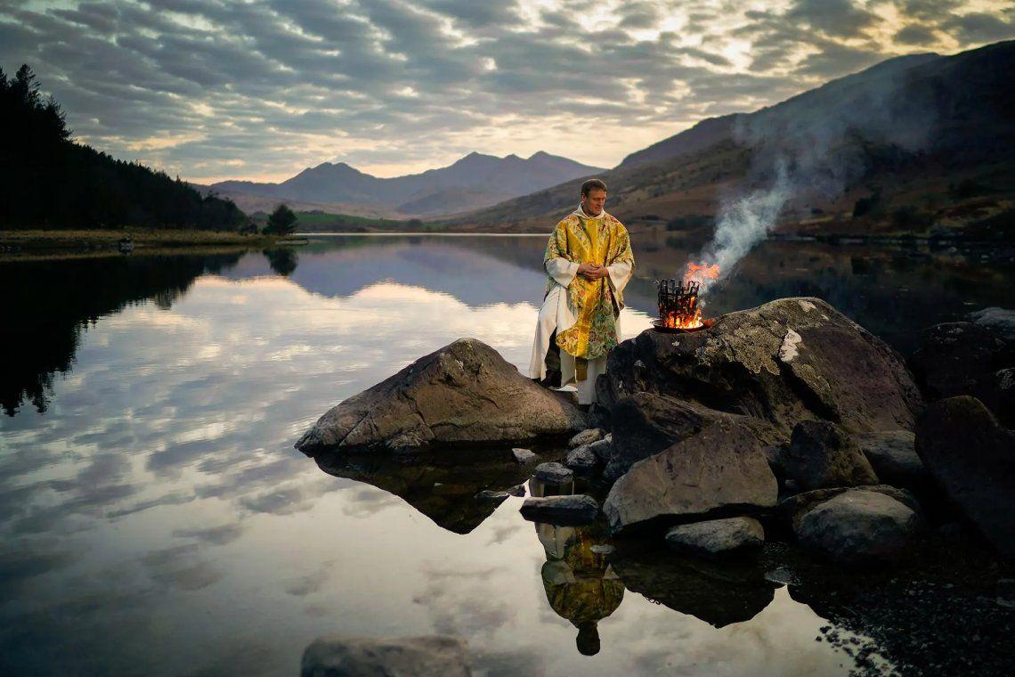Ganador del fotógrafo de retratos del año. El reverendo Stuart Elliott bendice el nuevo fuego como parte de su Servicio de Nueva Luz para la víspera de Pascua en la costa de Llynnau Mymbyr en Snowdonia en abril de 2020. Fotografía: Christopher Furlong