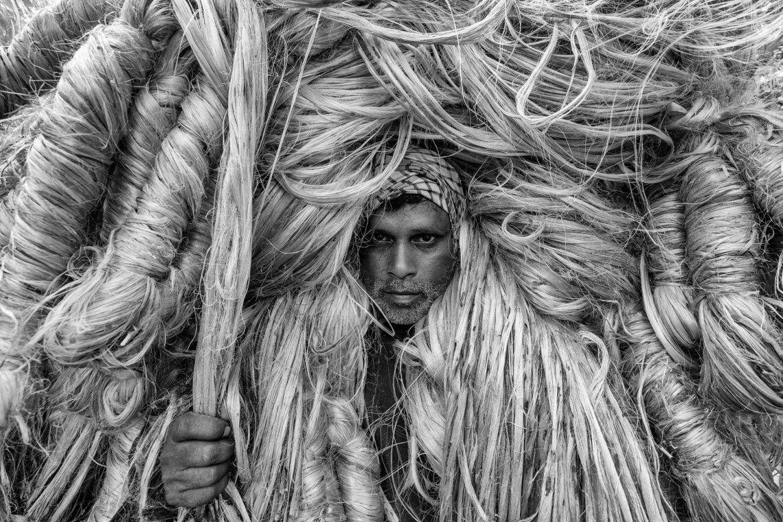 El hombre de fibras doradas. Los trabajadores parecen llevar grandes pelucas doradas mientras llevan a hombros bultos de yute de 50 kg. Fotografía: Azim Khan Ronnie