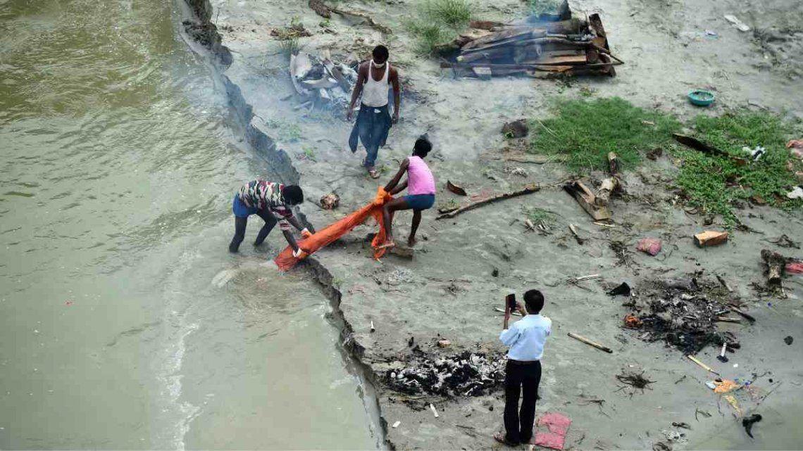 La policía y los equipos de rescate estatales patrullan en busca de cuerpos en el río.
