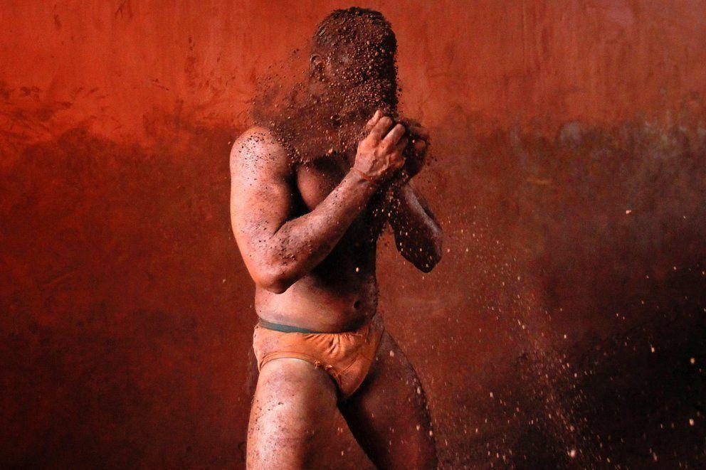 Un luchador se frota las manos con barro para evitar resbalar debido al sudor.