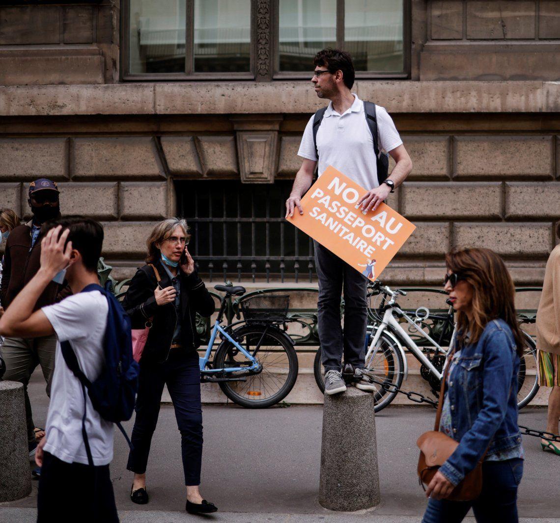 Un francés muestra una pancarta en rechazo al uso del pase sanitario.