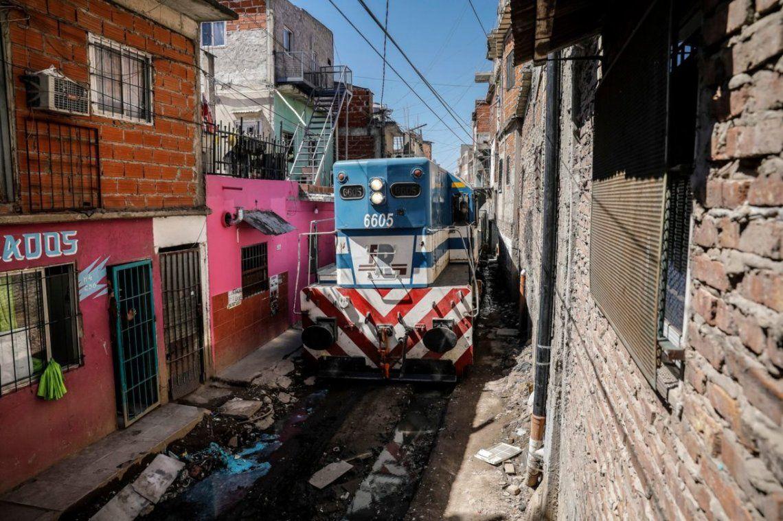 La formación de la empresa Ferrosur pasa a pocos centímetros de las casas del barrio.