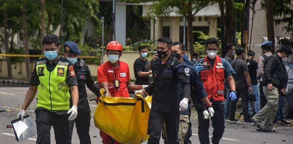 La policía transporta en una bolsa los restos de uno de los suicidas que hizo explotar la bomba junto a una iglesia cristiana en Macasar