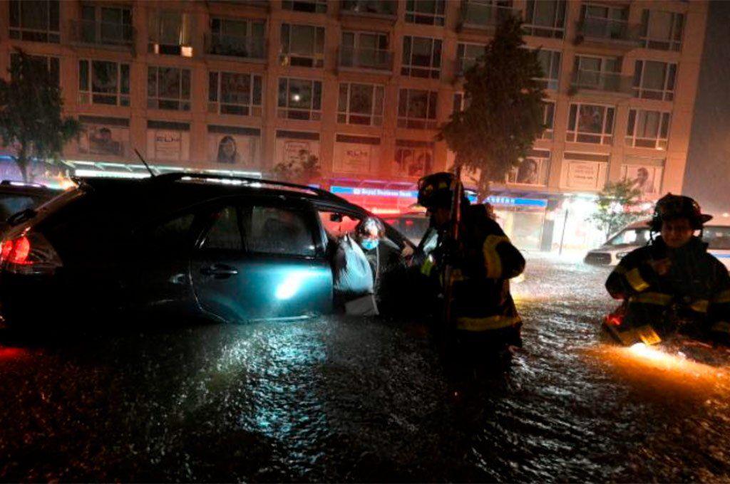 Bomberos de Nueva York rescatan a una mujer que quedó atrapada en su auto a causa de la repentina inundación de las calles.
