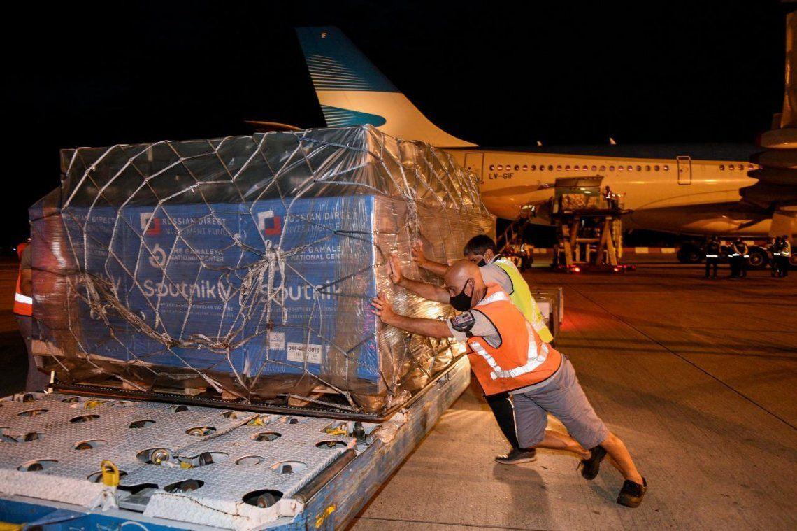 Operarios efectúan el desembarco de los contenedores de la vacuna Sputnik V.