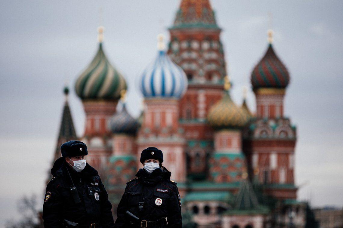 Dos policías rusos patrullan Moscú con su mascarilla para protegerse contra el coronavirus.